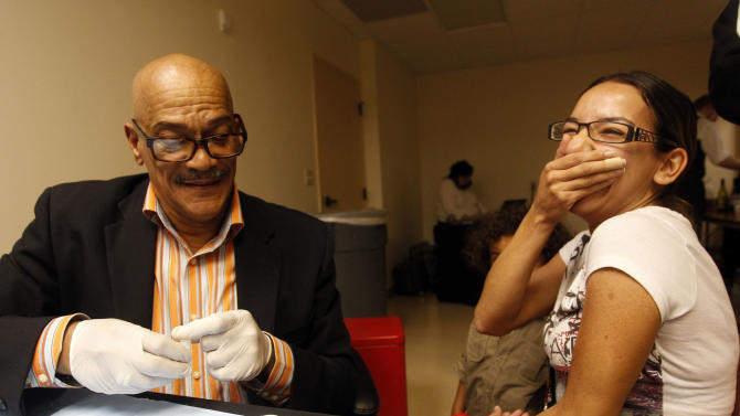 AHF HIV testing Counselor, Boyd Bowen demonstrates the Insti HIV-1 Antibody Test with the help of Danielle Botello at the Grand Opening of the new AHF Healthcare Center in Dallas, Tex. Monday, December 3, 2012. (Richard W. Rodriguez /AP Images for AIDS Healthcare Foundation)