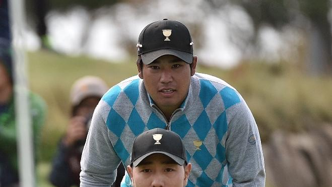Bae Sang-Moon of South Korea (bottom) and Kideki Matsuyama of Japan (top) study a putt on the 18th hole during the round three Foursome matches of the 2015 Presidents Cup at the Jack Nicklaus Golf Club in Incheon, west of Seoul, on October 10, 2015