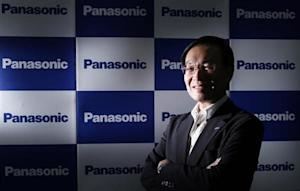 Panasonic Corp's President Tsuga poses in front of company logos after an interview with Reuters in Tokyo