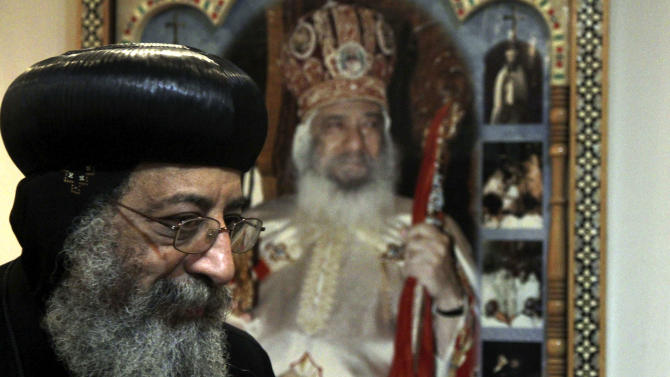 """FILE - In this Sunday, Nov. 4, 2012 file photo, Bishop Tawadros, 60, soon to be Pope Tawadros II  greets well-wishers, not shown, after being named the 118th Coptic Pope in the Wadi Natrun Monastery complex northwest of Cairo, Egypt. Egypt's Coptic Christian pope has sharply criticized the country's Islamist leadership in an interview with The Associated Press, Tuesday, Feb. 5, 2013, saying the new constitution is discriminatory and that Christians should not be treated as a minority. Pope Tawadros II also dismisses calls by President Mohammed Morsi for a national dialogue, saying, """"We will actively take part in any national dialogue that would benefit the nation, but when a dialogue ends before it starts and none of its results are implemented then we do not take part."""" (AP Photo/Roger Anis, El Shorouk Newspaper, File) EGYPT OUT"""