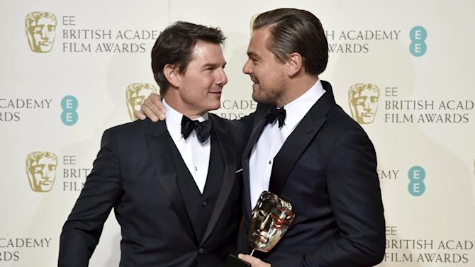 Leonardo DiCaprio holds his award for best leading actor as he embraces presenter Tom Cruise at the British Academy of Film and Television Arts (BAFTA) Awards at the Royal Opera House in London