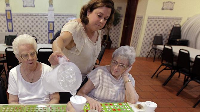 Cristina Couto, supervisor at the Ironbound Senior Center, pours cold water on the cup of Jenny Zeama, 84, bottom, as a group of elderly people play bingo at the city sponsored cooling station, Thursday, June 21, 2012, in Newark, N.J. Also seen are Evenlyn Maresca, 83, left, and Elsie Figueiredo, 93. Forecasters say temperatures could combine with humidity to make it feel like 110 degrees in parts of the state. Thermometers might not drop below 80 in the state's cities during the evening. (AP Photo/Julio Cortez)