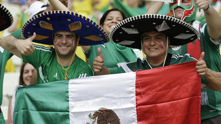 Mexico fans give thumb-up prior to the group A World Cup soccer match between Brazil and Mexico at the Arena Castelao in Fortaleza, Brazil, Tuesday, June 17, 2014. (AP Photo/Andre Penner)