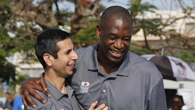 Former NBA player Dikembe Mutombo, right, and Orlando Magic's interim coach James Borrego share a laugh as they give a basketball training camp to children at an outdoor basketball court in the Vedado neighborhood of Havana, Cuba, Friday, April 24, 2015. Former NBA greats opened a four-day training camp, hoping to boost the game's popularity on the island following the declaration of detente between the U.S. and Cuba. (AP Photo/Desmond Boylan)