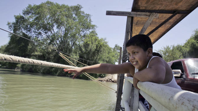 File - In this Aug. 8, 2007 file photo, Joe Cardenas, 9, reaches for the rope used to pull the hand drawn ferry between the U.S. and Mexico border at Los Ebanos, Texas. If Congress agrees on a comprehensive immigration reform bill, it will probably include a requirement to erect fencing that would wrap more of the nation's nearly 2,000-mile Southwest border in tall steel columns. But the mandate would essentially double down on a strategy that the Customs and Border Protection agency isn't even sure works. (AP Photo/LM Otero, File)