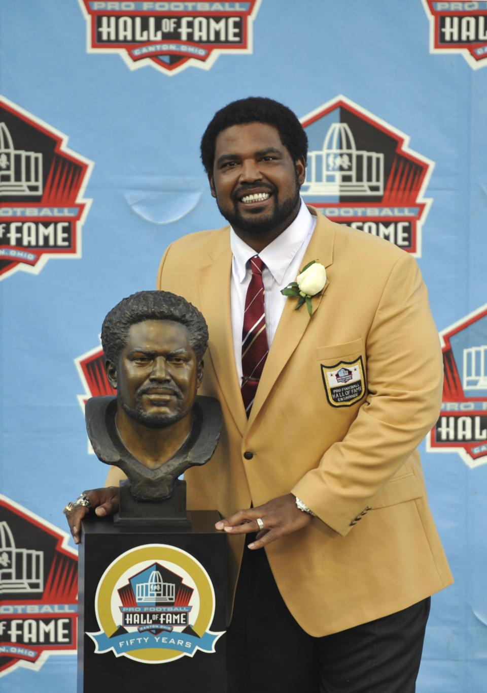 Hall of Fame inductee Jonathon Ogden poses with his bust during the 2013 Pro Football Hall of Fame Induction Ceremony Saturday, Aug. 3, 2013, in Canton, Ohio. (AP Photo/David Richard)