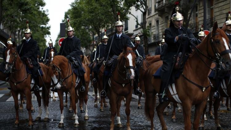 France's mounted Republican guards rest near the Champs Elysees avenue before a rehearsal of the Bastille day parade in Paris