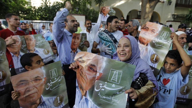 "Supporters of presidential candidate Ahmed Shafiq wave posters of him with Arabic that reads, ""Ahmed Shafiq for presidency, Egypt for all,"" in front of his campaign headquarters in Cairo, Egypt, Tuesday, June 19, 2012. A campaign spokesman for Hosni Mubarak's ex-prime minister said on Tuesday that Ahmed Shafiq has won the Egyptian presidential election, countering the Muslim Brotherhood's claims that its candidate was the winner. (AP Photo/Amr Nabil)"