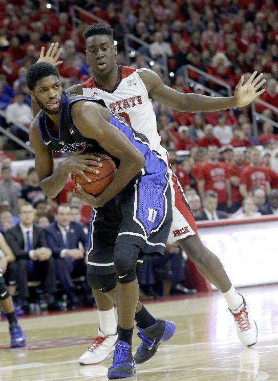 Duke's Amile Jefferson grabs the ball as North Carolina State's Abdul-Malik Abu defends during the first half of an NCAA college basketball game in Raleigh, N.C., Sunday, Jan. 11, 2015. (AP Photo/Gerry Broome)