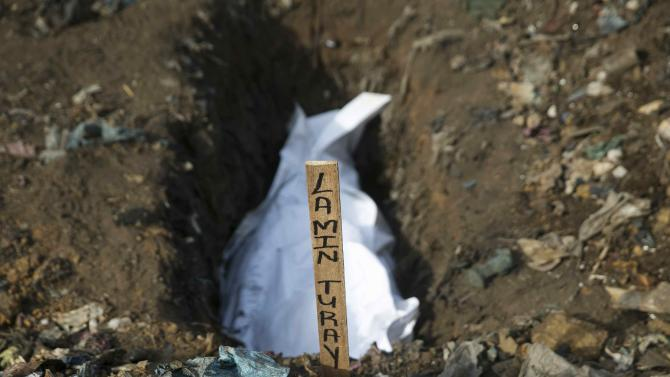 The body of a suspected Ebola victim awaits burial in a grave at a cemetery in Freetown