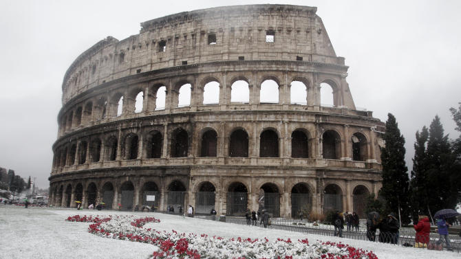 Snow surround the ancient Colosseum as snowflakes fell in Rome Friday, Feb. 3, 2012. Snowfalls are a rare occurrence for a capital usually blessed by a temperate climate, and other parts of the country experienced frigid temperatures unseen in years. The snowfall prompted authorities to stop visitors from entering the Colosseum, the Roman Forum and the Palatine Hill, the former home of Rome's ancient emperors. (AP Photo/Riccardo De Luca)