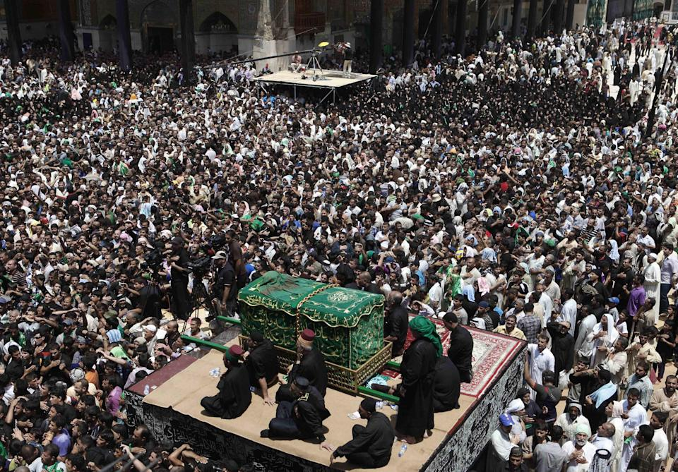 Shiite pilgrims carry a symbolic coffin at the holy shrine of the Imam Moussa al-Kadhim during the annual commemoration of the saint's death in the Shiite district of Kazimiyah, in Baghdad, Iraq, Saturday, June 16, 2012. (AP Photo/Karim Kadim)