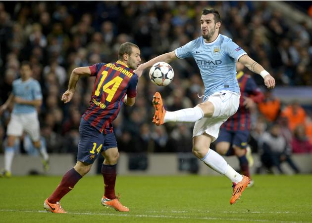 Manchester City's Alvaro Negredo challenges Barcelona's Javier Mascherano during their Champions League round of 16 first leg soccer match at the Etihad Stadium in Manchester