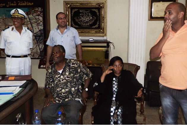 Rev. Michel Louis, 61, left, and 39-year-old Lissa Alphonse, second right, rest after their release at a police station in El Arish, in the northern part of Egypt's Sinai Peninsula, Monday, July 16, 2
