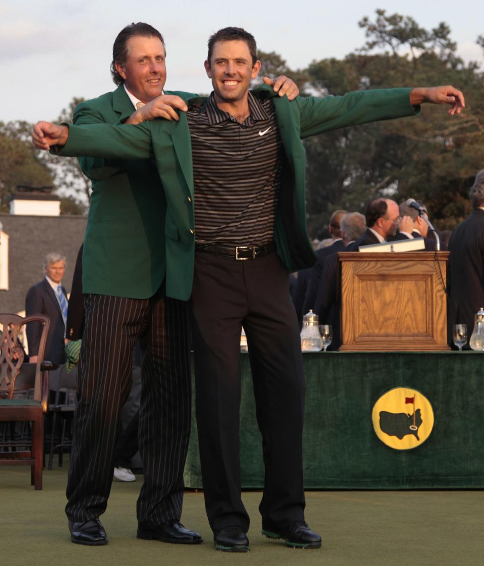Former champion Phil Mickelson, back, helps Charl Schwartzel of South Africa with his green Masters jacket after winning the Masters golf tournament Sunday, April 10, 2011, in Augusta, Ga.  (AP Photo/Charlie Riedel)