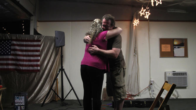 "In this Thursday, June 7, 2012 photo, Jason Moon, right, a veteran and singer-songwriter, gets a hug from Claudia Zuniga after his concert in Glendale, Calif. When Moon, who served in the Army in the Iraq War, plays his service-inspired music at concerts around the country, he sings of ""things I've seen I won't forget,"" about sacrifices that many warriors bear. (AP Photo/Jae C. Hong)"