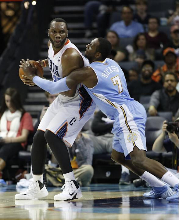 Charlotte Bobcats center Al Jefferson, left, looks to pass against Denver Nuggets center JJ Hickson during the second half of an NBA basketball game in Charlotte, N.C., Monday, March 10, 2014. Charlot