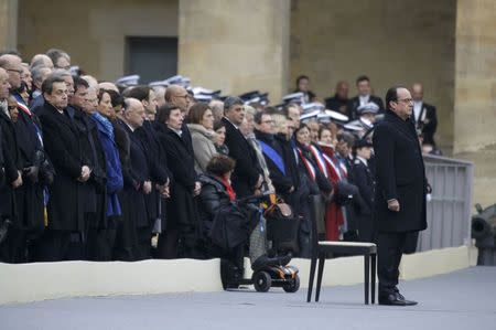 French President Francois Hollande stands in front of members of French government, French officials and guests during a ceremony to pay a national homage to the victims of the Paris attacks at Les Invalides monument in Paris