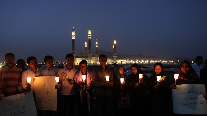 "FILE -- In this Monday, May 28, 2012 file photo, Yemenis hold candles during a rally to commemorate soldiers who were killed in a suicide bomb attack by suspected al-Qaida militants last week in Sanaa, Yemen. Al-Qaida committed ""horrific"" rights abuses during its 16 months in power between February 2011 and June 2012 in southern Yemen, the London-based rights group Amnesty International charged in a report released Tuesday. The report also accuses Yemen's government of abuses. The Arabic writing on the placards at left reads,""we will not allow you al-Qaida to kill our dreams,"" and at right,""our soldiers are our sons, what hurt to them hurt to us, we will not let them down and they will not let us down."" (AP Photo/Hani Mohammed, File)"