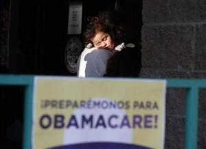 Esparza sleeps in the arms of her grandfather as they wait in line at a health insurance enrollment event in Cudahy, California