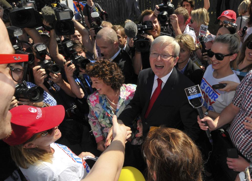 Australian Prime Minister Kevin Rudd, center right, and wife Therese Rein, center left, are greeted by well wishers after casting their votes in Brisbane, Australia Saturday, Sept. 7, 2013. Australians voted Saturday in a national election that is expected to see the Labor Party ousted from government after six years in power. (AP Photo/John Pryke)