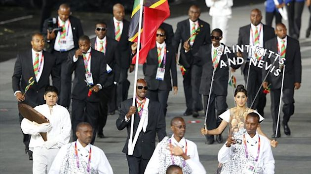 Saints Kitts and Nevis' flag bearer Kim Collins holds the national flag as he leads the contingent in the athletes parade during the opening ceremony of the London 2012 Olympic Games at the Olympic Stadium