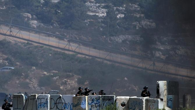 Israeli soldiers take cover during clashes with Palestinian demonstrators in the West Bank village of Betunia, on July 18, 2014