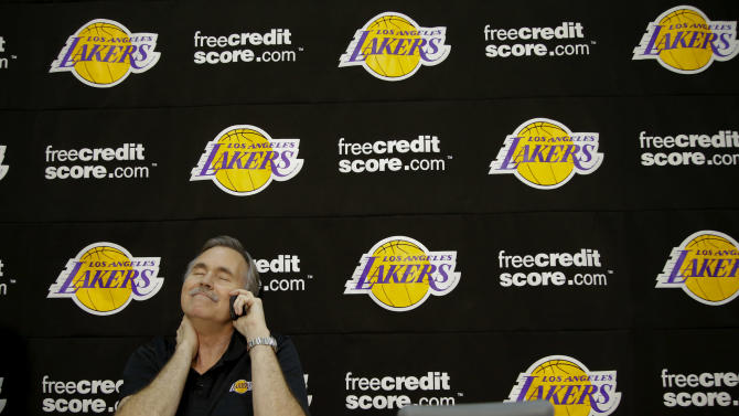 New Los Angeles Lakers coach Mike D'Antoni talks to a reporter on the phone after a news conference at the team's NBA basketball training facility in El Segundo, Calif., Thursday, Nov. 15, 2012. Although D'Antoni is still on crutches after his recent knee surgery, he is already at work with the Lakers. (AP Photo/Jae C. Hong)