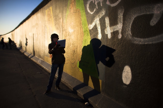 In early morning light, a radio broadcast journalist casts her shadow on the East Side Gallery named part of the former Berlin Wall as she reports about protests in Berlin, Monday, March 4, 2013. Afte