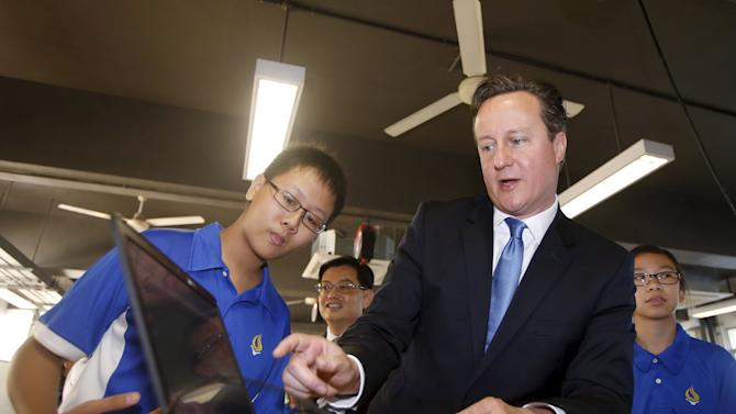 Britain's Prime Minister David Cameron speaks with students as he looks at a modelling software for 3D printers during a visit to Commonwealth Secondary School in Singapore