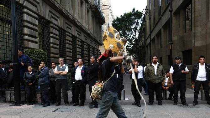A man wears a tiger mask during a demonstration to demand for justice in Mexico City