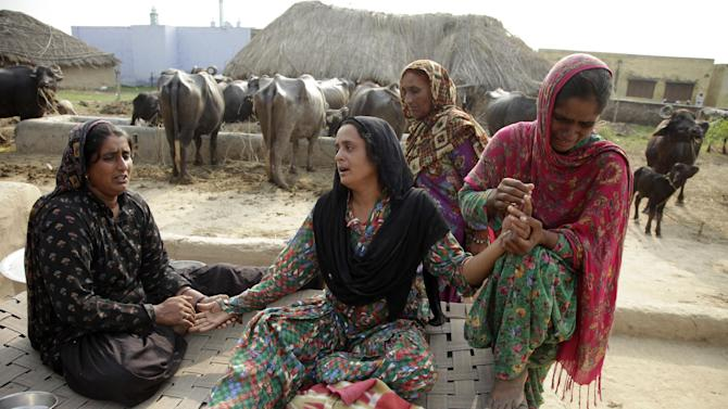 Relatives of Akram Hussain, a civilian killed in gunfire allegedly from the Pakistan side of the border, weep at their village in Ranbir Singh Pura region, about 35 kilometers (22 miles) from Jammu, India, Saturday, Aug. 23, 2014. India and Pakistan traded gunfire in the disputed Kashmir region on Saturday, killing two villagers on each side and wounding several others, officials said. Tensions have escalated in Kashmir since India earlier in the week called off diplomatic talks with Pakistan because the Pakistani ambassador in New Delhi met with separatist leaders from the disputed region. (AP Photo/Channi Anand)