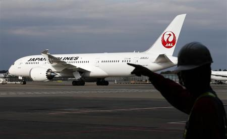 A staff of Japan Airlines' (JAL) walks past one of the company's Boeing Co's 787 Dreamliner plane at Narita international airport in Narita, east of Tokyo, November 11, 2013.