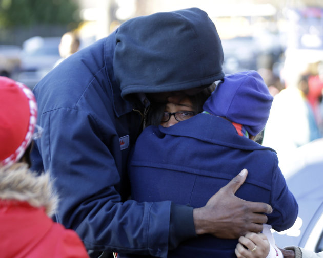 A man and a woman are reunited with a child a child after after a shooting at an Price Middle school in Atlanta Thursday, Jan. 31, 2013. A 14-year-old boy was wounded outside the school Thursday after