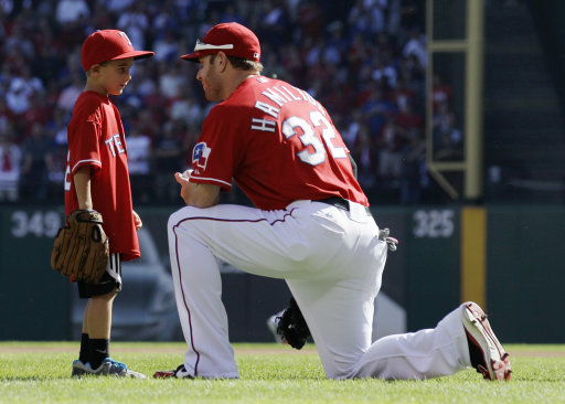 FILE - IN This Sept. 30, 2011, file photo, Cooper Stone, 6, left, talks with Texas Rangers left fielder Josh Hamilton (32) before Game 1 of baseball's American League division series playoffs in Arlington, Texas. Hamilton threw the ball Cooper's father Shannon Stone was reaching for when he fell to his death behind the outfield wall in July. Shannon Stones mother said Wednesday, Dec. 28, 2011, in Lubbock, Texas, that she  wants the star player to keep tossing souvenirs into the stands. (AP Photo/Tony Gutierrez, File)
