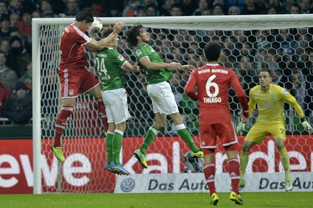 Bayern's Daniel van Buyten of Belgium, left, scores with his head during the German Bundesliga soccer match between Werder Bremen and Bayern Munich in Bremen, Germany, Saturday, Dec. 7, 2013