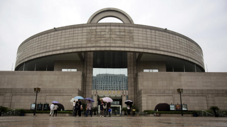 In this May 8, 2013 photo,  people walk outside of the Shanghai Museum in Shanghai, China. Many items from its extensive collections of porcelains, jades, paintings and bronzes were donated by families that fled to Hong Kong following the 1949 communist victory but have since reconciled with the mainland.  (AP Photo/Eugene Hoshiko)