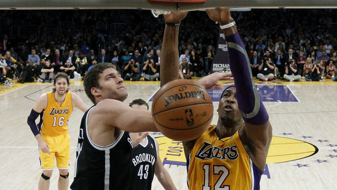 Los Angeles Lakers' Dwight Howard, right, dunks against Brooklyn Nets' Brook Lopez, left, in the first half of an NBA basketball game in Los Angeles, Tuesday, Nov. 20, 2012. (AP Photo/Jae C. Hong)