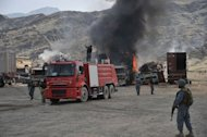 Afghan security personnel guard burning military vehicles after a clash between Taliban and Afghan security forces in Torkham on September 2, 2013. Taliban suicide bombers and gunmen dressed as Afghan police attacked a US base in Torkham near the Pakistani border on Monday, sparking a shootout that left all three assailants dead, officials said