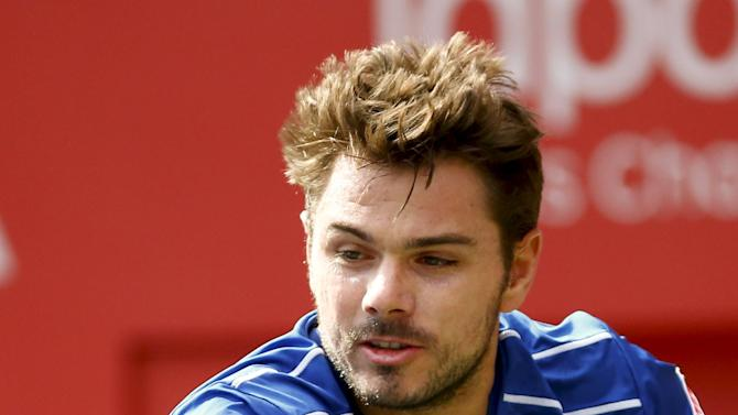 Switzerland's Stan Wawrinka returns the ball to Austin Krajicek of the U.S. during their men's singles tennis match at the Japan Open championships in Tokyo
