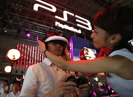 File photo of a promoter helping a visitor try out new game software on Sony's PlayStation 3 game console at the Tokyo Game Show in Chiba
