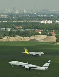 An Israeli El Al aircraft takes off as a German Wings aircraft taxis down the runway at Schoenefeld Airport in Berlin, last month. Airlines flying to, from or within the European Union are required to monitor CO2 emissions for entire journeys and, if necessary, pay for exceeding their carbon allowances