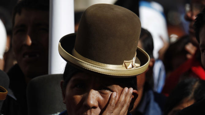 A woman listens to Bolivia's President Evo Morales talk during the annual May Day march in La Paz, Bolivia, Wednesday, May 1, 2013. Morales said Wednesday he is expelling the USAID from Bolivia for allegedly seeking to undermine his leftist government. (AP Photo/Juan Karita)