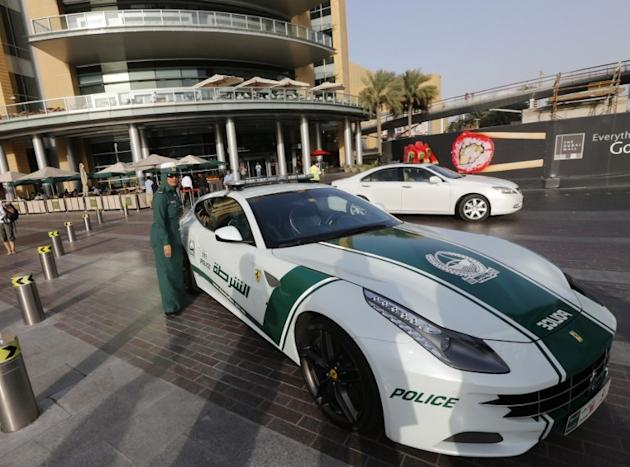 An Emirati female police officer stands near a Ferrari police vehicle on April 25, 2013 in the Gulf emirate of Dubai. Dubai police showed off a new Ferrari they will use to patrol the city state, hot