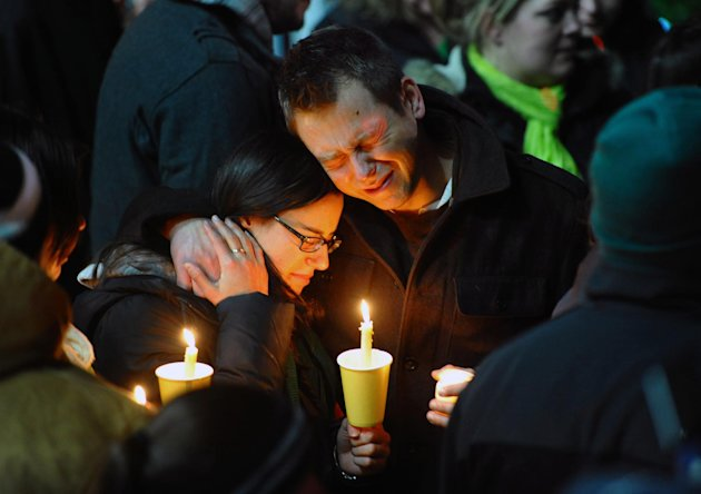 Ted Kowalczuk, of Milford, Conn., and his friend Rachel Schiavone, of Norwalk, Conn., attend a candlelight vigil held behind Stratford High School on the Town Hall Green in Stratford, Conn. on Saturda