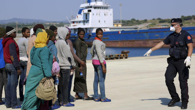 An Italian Carabiniere policeman instructs some migrants after they disembarked from the Italian Coast Guard vessel Peluso arrived in the Sicilian port town of Augusta, Wednesday, June 3, 2015. Some 406 migrants were taken to Sicily after being rescued at sea in the Sicily Channel. (AP Photo/Francesco Malavolta)