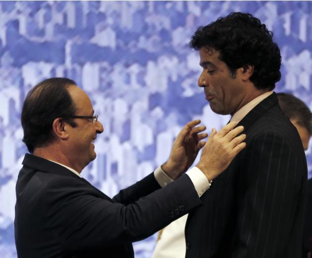 France's President Francois Hollande decorates former PSG soccer star Rai Souza de Oliveira of Brazil in Sao Paulo