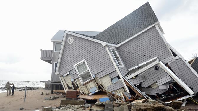 FILE - In this Tuesday, Oct. 30, 2012 file photo, people stand next to a house collapsed from Superstorm Sandy in East Haven, Conn. While Connecticut was spared the destruction seen in New York and New Jersey, many communities along the shoreline, including some of the wealthiest towns in America, were struggling with one of the most severe storms in generations. (AP Photo/Jessica Hill, File)
