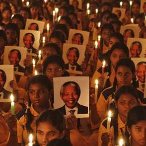 Schoolchildren hold candles and portraits of former South African President Mandela during prayer ceremony at school in Chennai