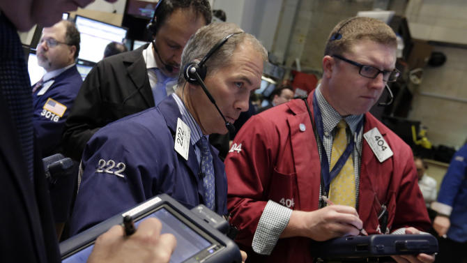 Timothy Nick, center, works with fellow traders on the floor of the New York Stock Exchange Tuesday, March 19, 2013. A surprisingly strong increase in new home construction is sending stocks higher in early trading on Wall Street. (AP Photo/Richard Drew)